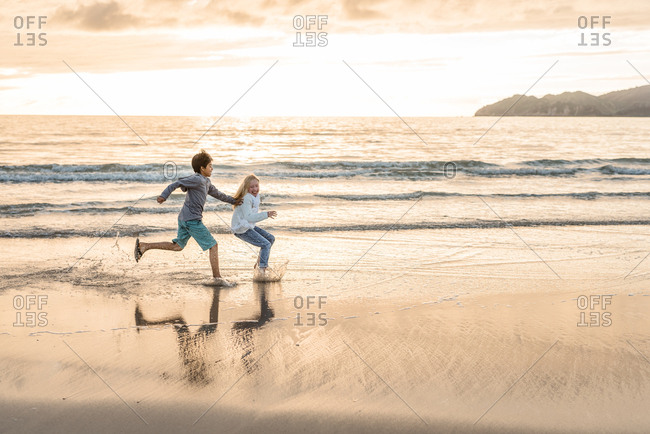 Boy chasing his sister on a beach at sunset