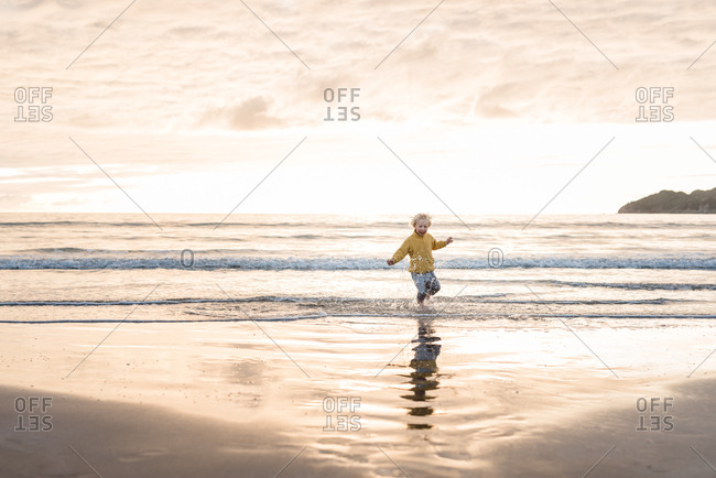 Boy splashing in the water on a beach at sunset
