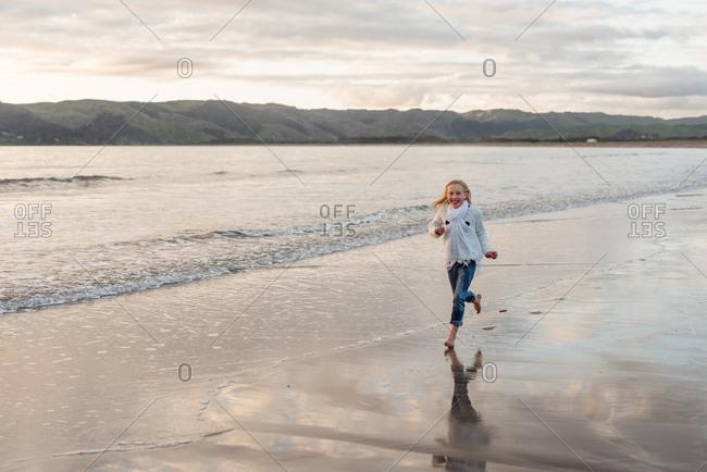 Blonde girl running on a beach at sunset