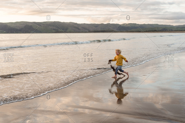 Boy playing with seaweed on a beach at sunset