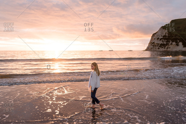 Blonde girl on a beach at sundown