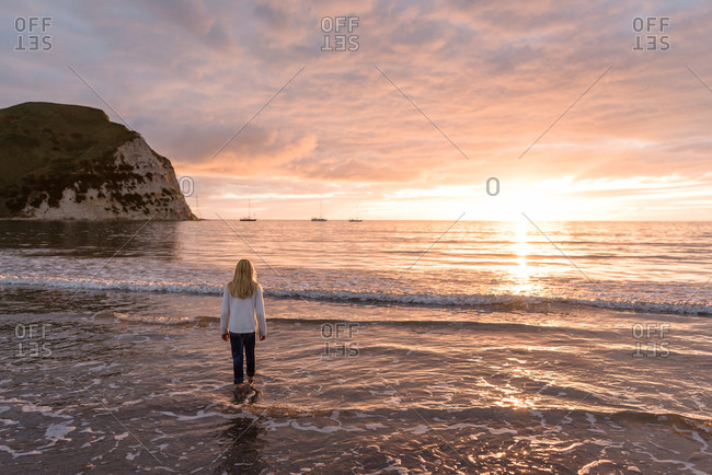 Blonde girl on a beach looking out to sea at sundown