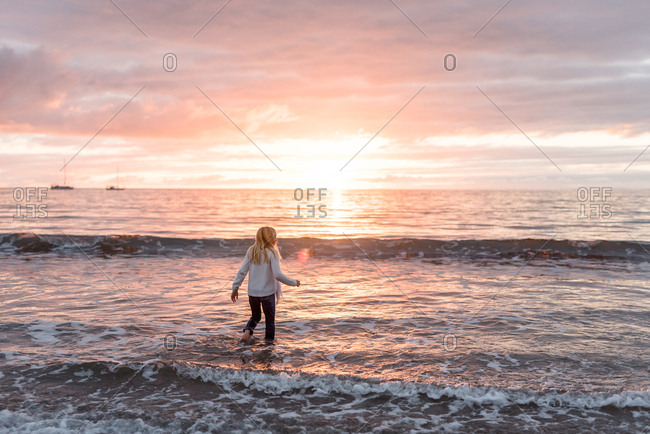 Blonde girl walking in the waves on a beach at sundown
