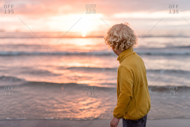 Little boy looking out at waves on a beach at sundown