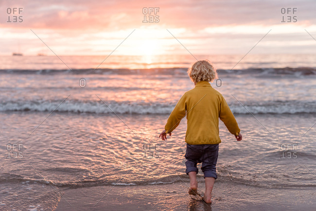Rear view of a little boy on a beach at sundown