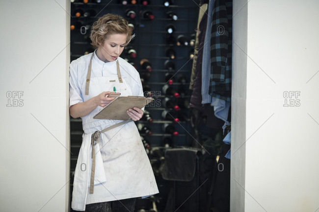 Female restaurant owner using smart phone standing with clipboard on doorway