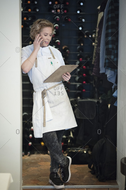 Full length of female restaurant owner talking on mobile phone standing with clipboard on doorway