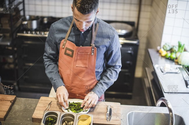 High angle view of young chef preparing food in plate at kitchen counter in restaurant