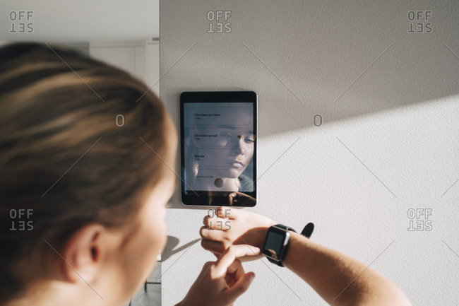 Teenage girl adjusting smart watch with digital tablet mounted on white wall at home