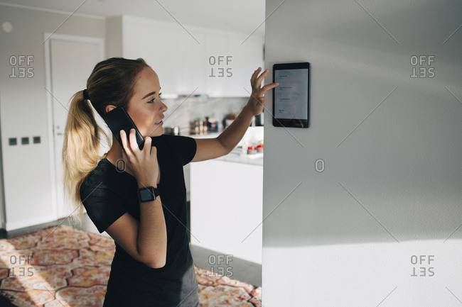 Teenage girl talking on smart phone while using digital tablet mounted on white wall at home