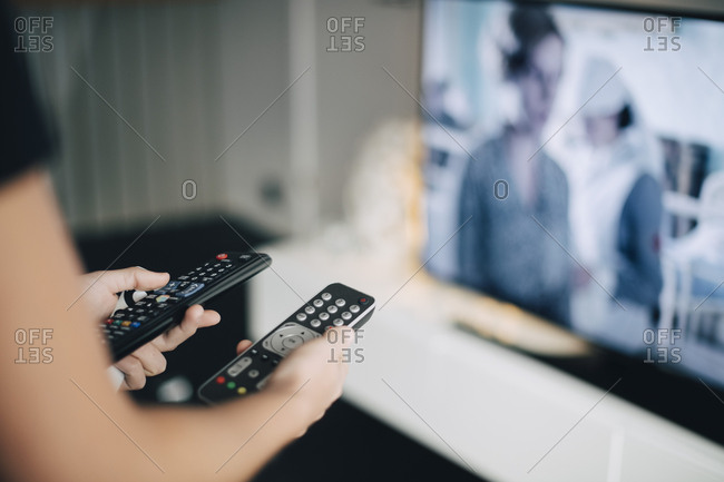 Midsection of teenage girl holding remote controls by television set in living room at home