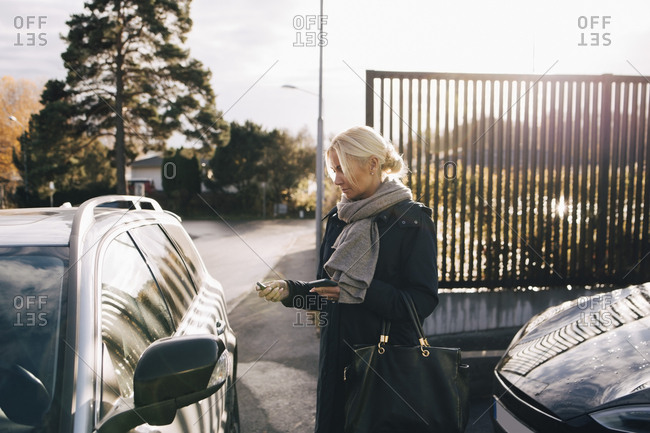 Mature woman standing by car against sky