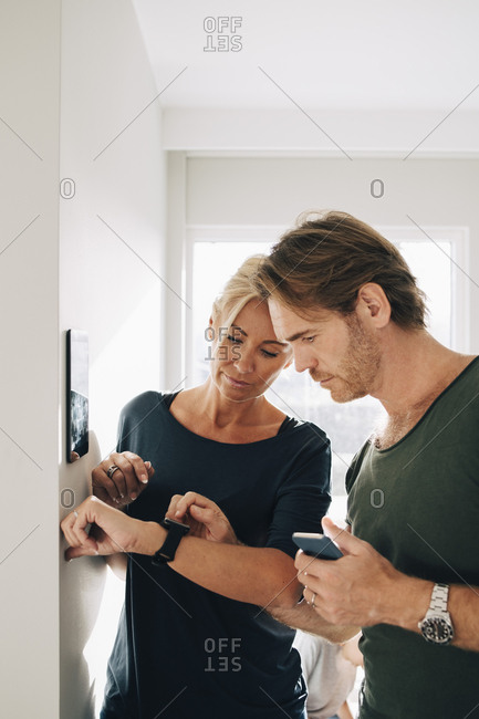 Mature couple adjusting smart watch with digital tablet mounted on wall at home