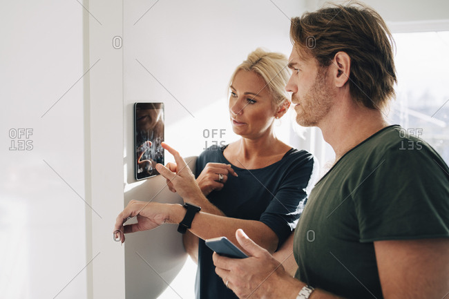 Mature couple adjusting digital tablet mounted on wall at home