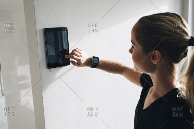 Teenage girl using tablet mounted on white wall at home