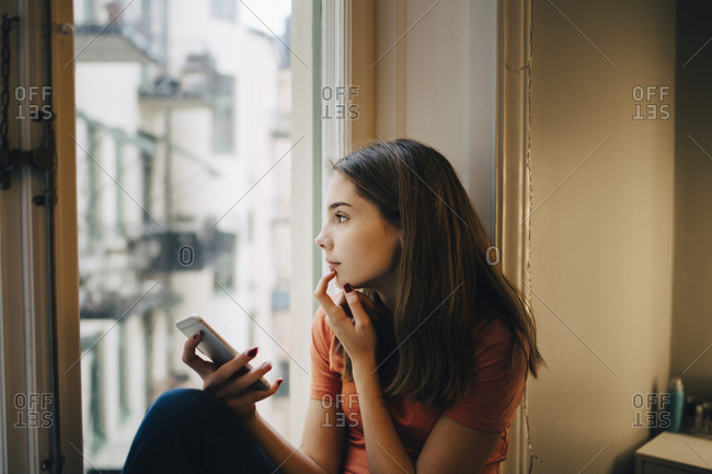 Thoughtful girl using phone while sitting at window sill
