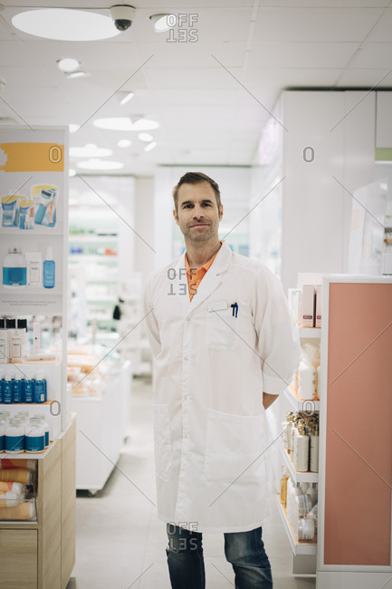 Portrait of confident mature male pharmacist standing at medical store
