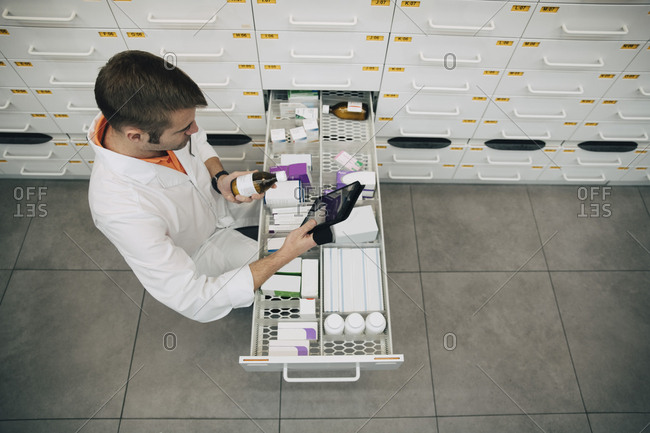 High angle view of pharmacist holding digital tablet checking medicine bottle at store