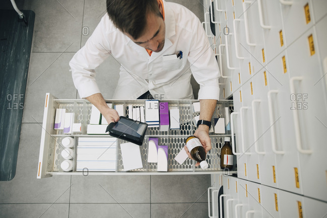 High angle view of pharmacist checking medicine bottle with digital tablet at store