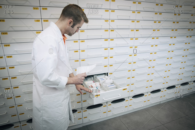 Side view of mature male pharmacist holding prescription paper standing by medicines in drawer at store