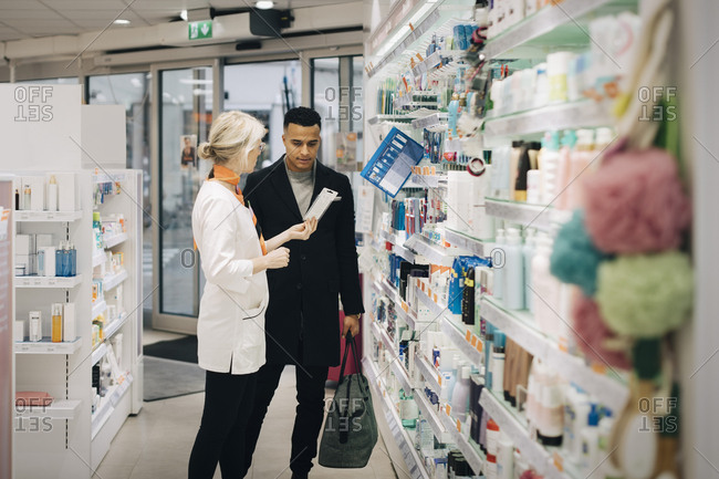 Side view of mature female pharmacist assisting male customer standing by rack at medical store
