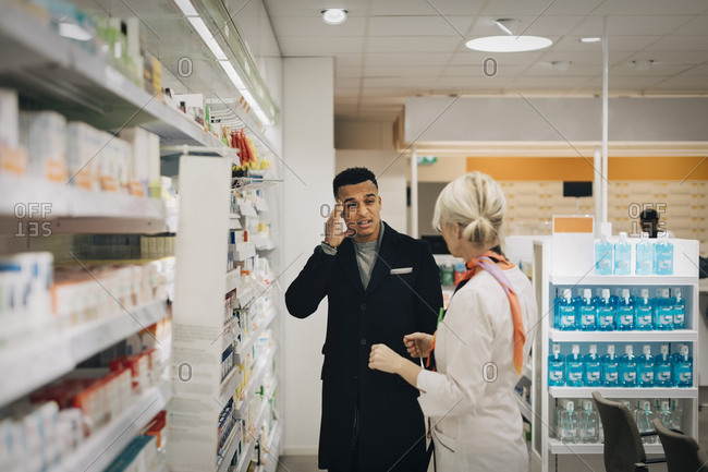 Male customer explaining headache to female pharmacist standing by rack at store