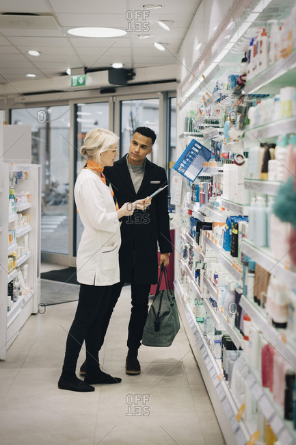 Full length of mature female pharmacist assisting male customer standing by rack at medical store