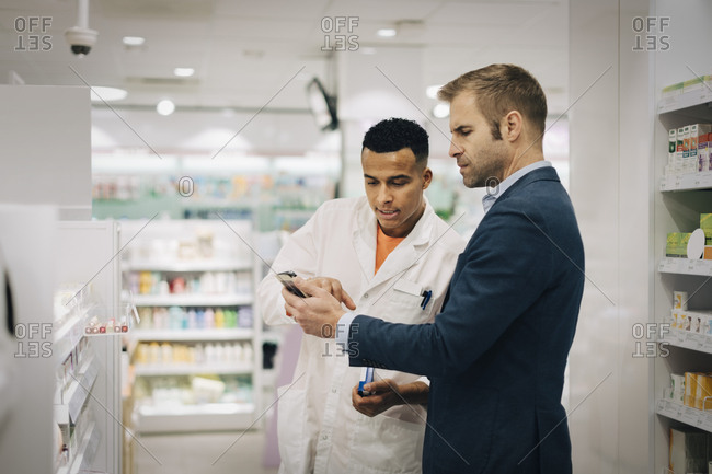 Mature customer showing mobile phone to male pharmacist standing at medical store