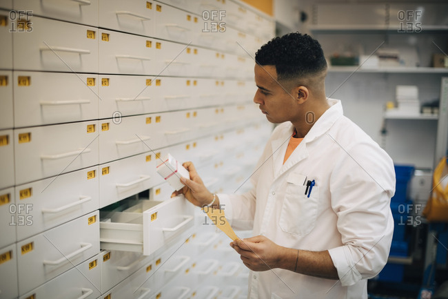 Confident male owner checking medicine from drawer in pharmacy store