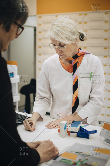 Mature female pharmacist writing on prescription paper at checkout with senior customer in medical store