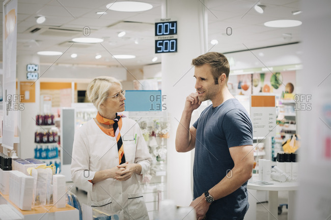 Male customer talking with female owner at pharmacy store