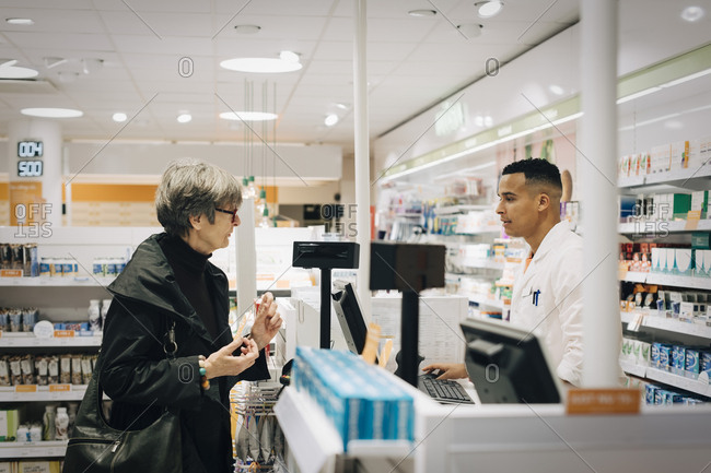 Side view of senior female customer talking with male pharmacist at checkout in store