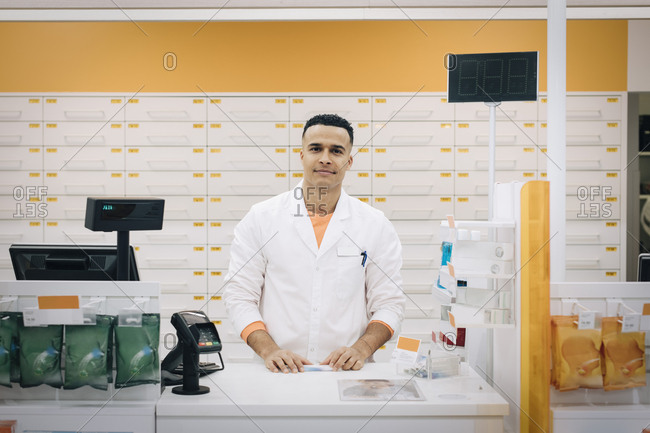 Portrait of confident male pharmacist standing at checkout at medical store