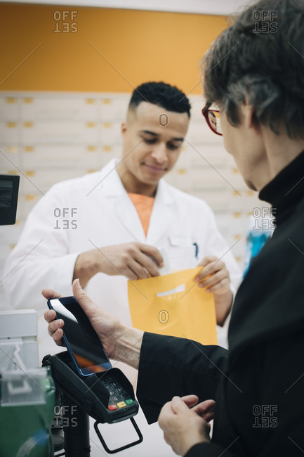 Senior female customer using contactless payment through mobile phone against pharmacist at checkout in store