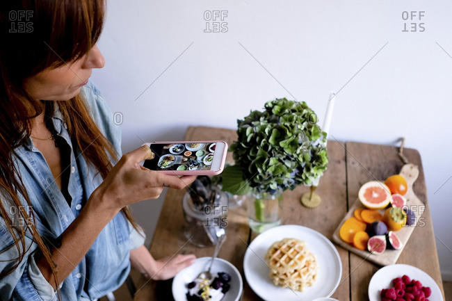 High angle view of female blogger photographing food at table through mobile phone by wall