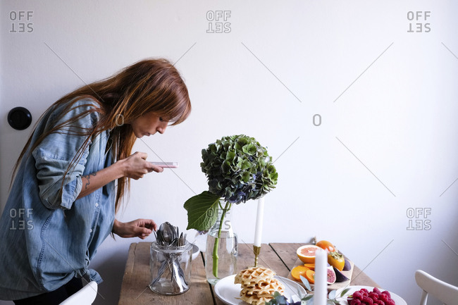 Side view of blogger photographing food at table through mobile phone by wall