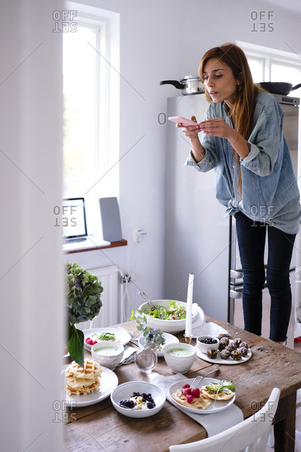 Blogger photographing food at table through mobile phone by window