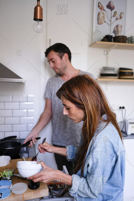 Man and woman preparing food while standing by counter in kitchen