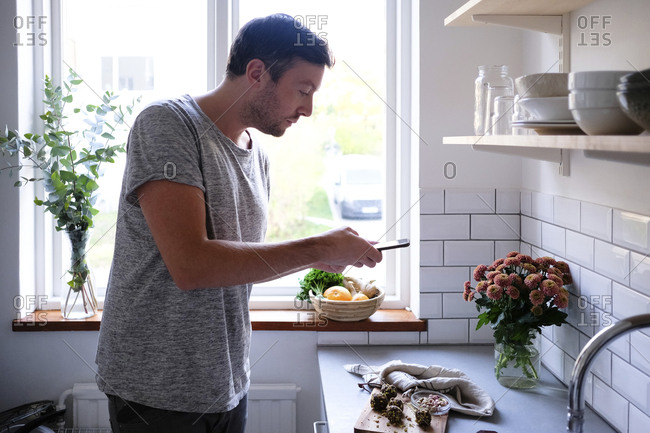 Mid adult man photographing food through smart phone at kitchen counter