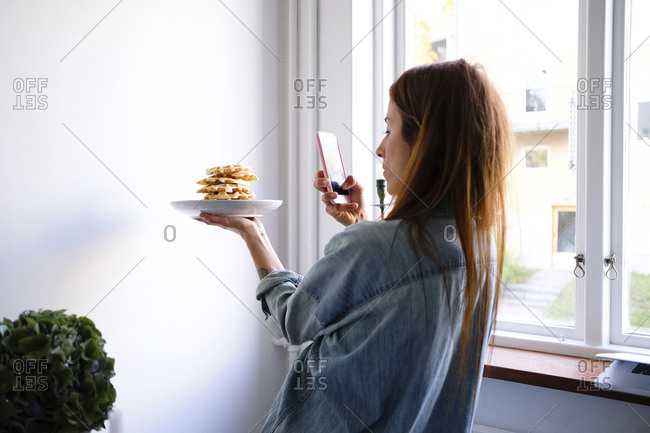 Woman photographing waffles through smart phone in plate by wall at home