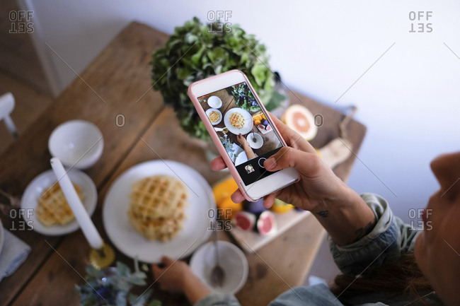 High angle view of woman photographing waffles in plate on table at home