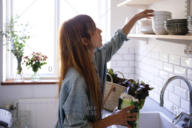 Side view of woman holding vegetables while looking at bowls on shelf in kitchen