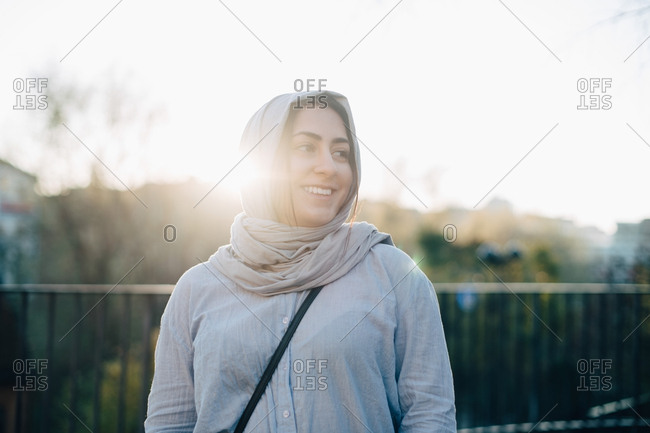 Back lit of smiling young Muslim woman wearing hijab against sky
