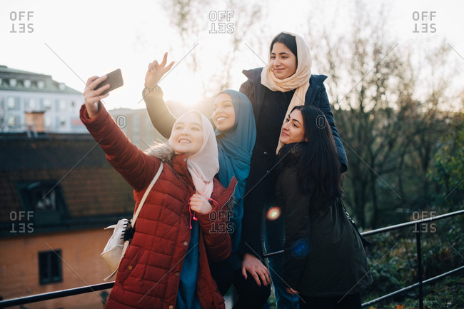 Happy young Muslim woman taking selfie with friends by railing in city