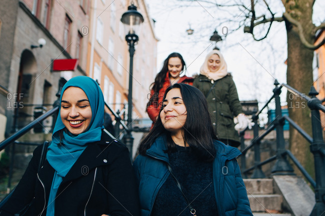 Low angle view of smiling multi-ethnic female friends moving down on staircase in city