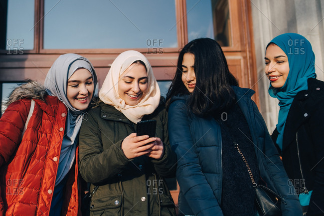 Happy female Muslim friends sharing smart phone standing against entrance door in city