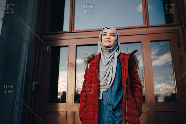 Low angle view of confident young Muslim woman standing against entrance door in city