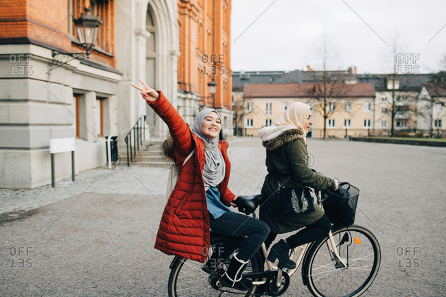 Portrait of happy young woman showing peace sign sitting behind friend on bicycle in city