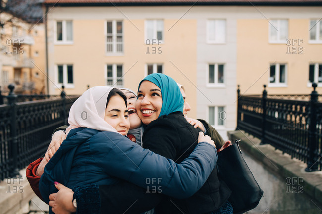 Cheerful multi-ethnic female Muslim friends embracing in city