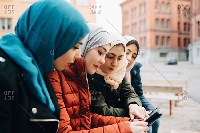 Female friends wearing hijabs sitting in city sharing digital tablet